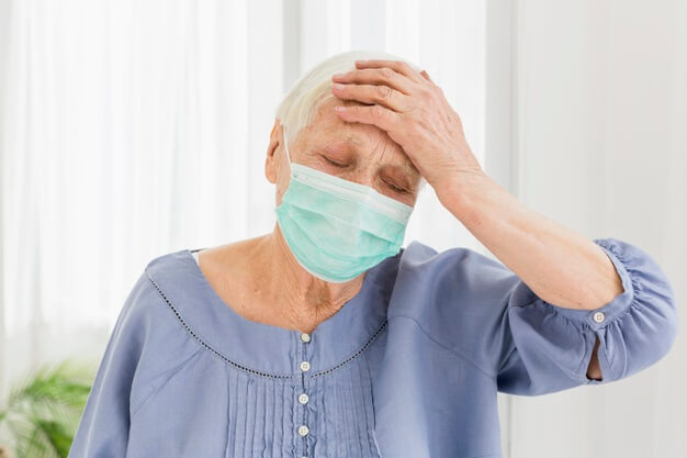 An unwell old lady wearing a surgical mask